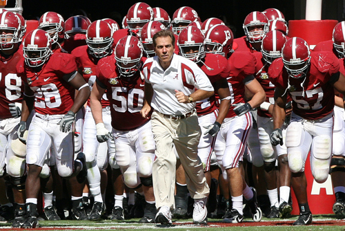 Coach Nick Saban leading Alabama's Crimson Tide football team as they run into the stadium.