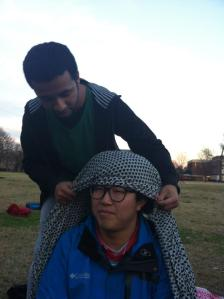Ibrahim wrapping a scarf around his Korean friend's head to show how Saudis have to wrap their heads when they make their way into the desert.